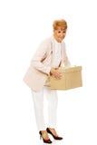 Mujer de negocios mayor de la sonrisa que sostiene la caja de cartón Foto de archivo libre de regalías