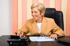 Mujer de negocios mayor de risa que usa la calculadora Fotografía de archivo