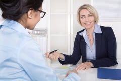 Mujer de negocios mayor en la entrevista con un aprendiz - uso fotografía de archivo