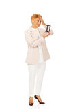 Mujer de negocios mayor preocupante con la palma en su frente que sostiene el reloj de arena foto de archivo libre de regalías