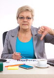 Mujer de negocios mayor que muestra los pulgares abajo y que trabaja en su escritorio en la oficina, concepto del negocio Imagenes de archivo
