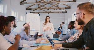 Mujer de negocios milenaria experimentada de los jóvenes que habla ante el equipo creativo de oficinistas, seminario de entrenami almacen de video