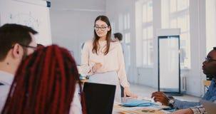 Mujer de negocios milenaria joven en los vidrios que hablan al equipo enfocado profesional de la raza mixta de socios de la empre almacen de video