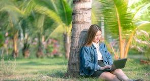 Mujer de negocios moderna o trabajo acertado en el ordenador portátil y el cuaderno en el lugar creativo al aire libre Fotografía de archivo
