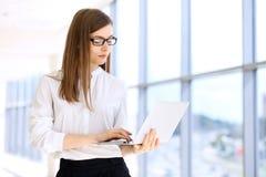 Mujer de negocios moderna que mecanografía en el ordenador portátil mientras que se coloca en la oficina antes de encontrar o de  Imagen de archivo