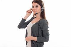 Mujer de negocios morena bonita joven con los auriculares y el micrófono que miran la cámara aislada en el fondo blanco Fotos de archivo