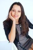 Mujer de negocios morena sonriente joven que se sienta en una silla Fotografía de archivo