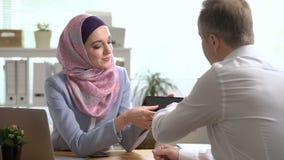 Mujer de negocios musulmán joven y hombre caucásico que trabajan con la tableta en oficina almacen de video