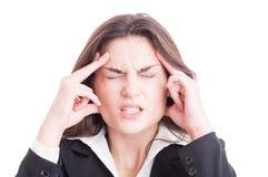 Mujer de negocios o encargado financiero que tiene un dolor de cabeza agotador Imágenes de archivo libres de regalías