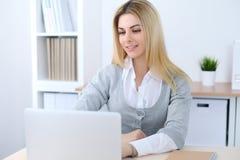 Mujer de negocios o muchacha joven del estudiante que se sienta en el lugar de trabajo de la oficina con el ordenador portátil Co Imagen de archivo