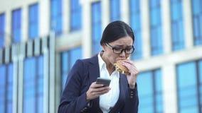 Mujer de negocios ocupada que envía el correo electrónico por el smartphone, hamburguesa que muerde, hora de la almuerzo imagen de archivo