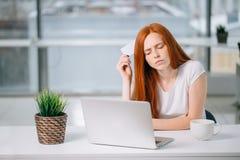 Mujer de negocios de pensamiento que se sienta en la tabla con el ordenador portátil, sosteniendo la tarjeta de crédito vacía foto de archivo libre de regalías