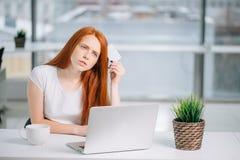 Mujer de negocios de pensamiento que se sienta en la tabla con el ordenador portátil, sosteniendo la tarjeta de crédito vacía imagenes de archivo