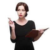 Mujer de negocios pensativa con el diario Imagenes de archivo