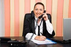 Mujer de negocios por el teléfono que toma notas Fotografía de archivo libre de regalías