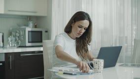 Mujer de negocios que analiza el lugar de trabajo de las cartas de los datos financieros en casa almacen de video