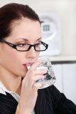 Mujer de negocios que bebe el agua mineral Imagenes de archivo