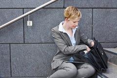 Mujer de negocios que busca ficheros en cartera Foto de archivo libre de regalías