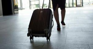 Mujer de negocios que camina con el bolso rodado metrajes