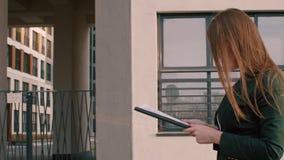 Mujer de negocios que camina en la calle de la ciudad y que lee documentos de negocio almacen de metraje de vídeo