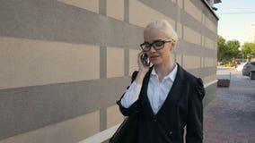 Mujer de negocios que camina y que hace una llamada de teléfono al aire libre en ciudad almacen de video
