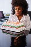 Mujer de negocios que celebra la fiesta de cumpleaños en la oficina que sopla Cand Fotos de archivo libres de regalías