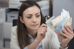 Mujer de negocios que comprueba la autenticidad del dinero fotografía de archivo