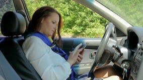 Mujer de negocios que conduce y con el teléfono almacen de video
