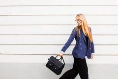 Mujer de negocios que corre en un traje con una cartera a lo largo de la pared imágenes de archivo libres de regalías