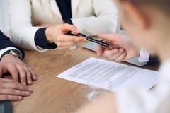 Mujer de negocios que da la pluma al hombre de negocios listo para firmar el contrato Comunicación del éxito en la reunión o la n foto de archivo