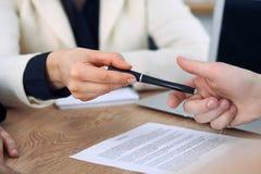 Mujer de negocios que da la pluma al hombre de negocios listo para firmar el contrato Comunicación del éxito en la reunión o la n foto de archivo libre de regalías