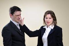 Mujer de negocios que da una palmada al hombre en oficina Fotografía de archivo