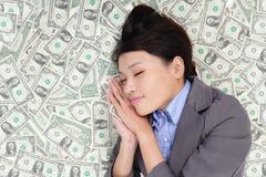 Mujer de negocios que duerme en cama del dinero Imagenes de archivo