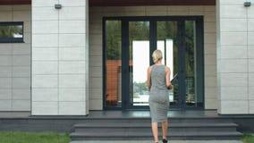 Mujer de negocios que entra en la puerta de lujo de la oficina con el ordenador almacen de metraje de vídeo