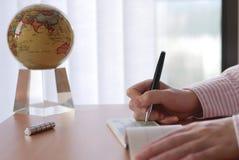 Mujer de negocios que escribe un cheque con el giro del globo imagen de archivo libre de regalías