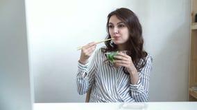 Mujer de negocios que goza de la ensalada fresca para la hora de la almuerzo en el escritorio de oficina almacen de metraje de vídeo