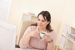 Mujer de negocios que goza del café en la oficina moderna Imágenes de archivo libres de regalías