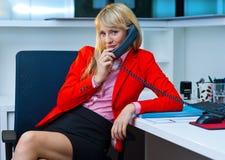 Mujer de negocios que habla con el teléfono en oficina Fotos de archivo libres de regalías