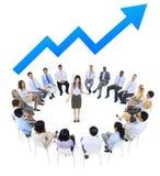 Mujer de negocios que habla con los hombres de negocios y la línea gráfico arriba Fotografía de archivo