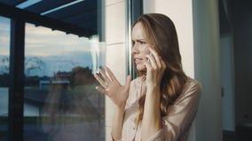 Mujer de negocios que habla el tel?fono m?vil Mujer nerviosa que explica su posición almacen de video