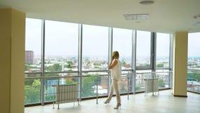 Mujer de negocios que habla en el teléfono en oficina vacía con paisaje urbano en fondo metrajes