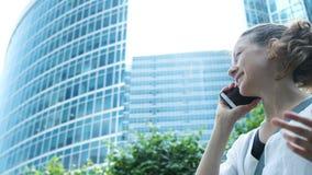 Mujer de negocios que habla en el teléfono y que gesticula con la mano en el fondo de rascacielos almacen de metraje de vídeo