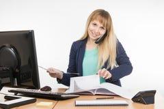 Mujer de negocios que habla en el teléfono y que busca los documentos de papel deseados Fotografía de archivo