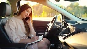 Mujer de negocios que habla en un smartphone y que toma notas en la lechería que se sienta en el coche metrajes