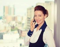 Mujer de negocios que habla en ventana de la oficina del teléfono que hace una pausa móvil con el fondo urbano de la ciudad Imágenes de archivo libres de regalías