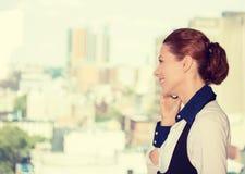 Mujer de negocios que habla en ventana de la oficina del teléfono que hace una pausa móvil con el fondo urbano de la ciudad Fotografía de archivo