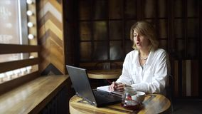 Mujer de negocios que hace la llamada video en cafetería metrajes
