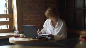 Mujer de negocios que hace notas en un diario en un café metrajes