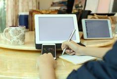 Mujer de negocios que hace notas y que usa una tableta Imagenes de archivo