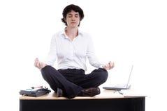 Mujer de negocios que hace yoga en su escritorio Fotos de archivo libres de regalías